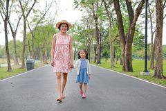Mam? feliz e filha asi?ticas que andam na rua no parque do ver?o fotos de stock
