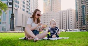 Mam? joven con el beb? que se sienta en la hierba en el parque que come el almuerzo metrajes