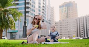 Mam? joven con el beb? que se sienta en la hierba en el parque que come el almuerzo almacen de metraje de vídeo