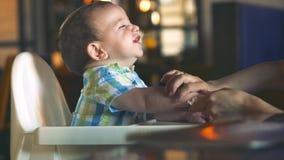 A mam? limpa suas boca e m?os no beb? ador?vel Risos encantadores e aplausos de uma crian?a Bebê pequeno bonito que come a filme