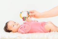 Mamã que dá a um chocalho seu bebê pequeno Imagem de Stock