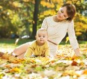 Mamã que encontra-se nas folhas com bebê Fotos de Stock Royalty Free