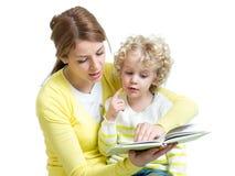 Mamá que lee un libro para embromar Imagen de archivo libre de regalías