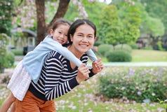 Mam? sonriente que lleva a su muchacha del peque?o ni?o en jard?n con completamente la flor del rosa de la ca?da alrededor Famili foto de archivo