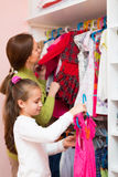 Mam teaching girl to choose clothes Royalty Free Stock Photos