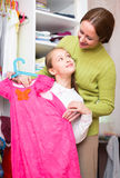 Mam teaching girl to choose clothes Royalty Free Stock Image
