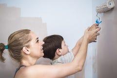 Mam teachs jej 3 roku syna obrazu z rolownikiem w domu obrazy stock