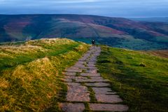 Mam Tor Trail, Peak District, England. A man walks a stone trail at sunrise to the summit of Mam Tor, a part of the Great Ridge, in the Peak District National royalty free stock photography