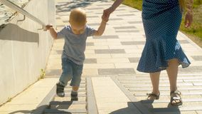 Mama with baby boy walking up the stairs stock video footage