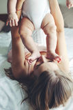 Mama with baby. Portrait of beautiful mom playing with her baby in bedroom. Kissing baby's feet Stock Image