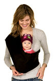 Mama with Baby in Sling. Mom holding her baby who is making a funny face in a sling Stock Photo