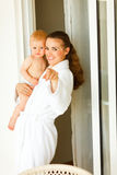 Mama in bathrobe with baby pointing in camera Royalty Free Stock Photos