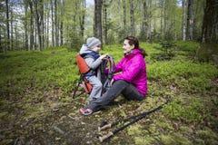 Mama chodzi w lesie z dzieckiem, dziecko w dzieciach niesie Zdjęcia Stock
