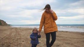 Mama chodzi wzdłuż plaży z jej małym synem który ostatnio uczył się chodzić zbiory