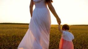 Mama chodzi z jej małą córką i trzyma dziecka ręcznie Szczęśliwy rodzinny odpoczywać w parku w lecie w promieniach ciepły zbiory