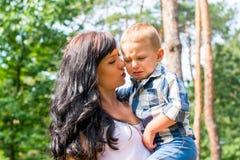Mama chwyty w jej rękach i pocieszają jej chłopiec która płacze, Fotografia Stock