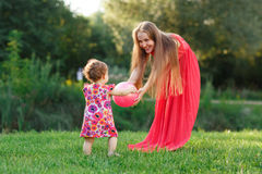 Mama with daughter play and ball on grass in park. Mama with small daughter play with ball on grass in park Royalty Free Stock Photography