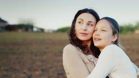 Mama delikatnie ściska jej córki dla 11 roku Wpólnie patrzeją w jeden kierunku położenia słońce Wartości rodzinne zbiory