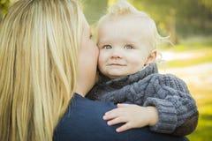 Mama, die ihr entzückendes blondes Baby umfasst Stockbild