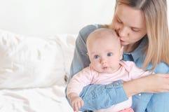 Mama, die ihre Tochter auf weißem Hintergrund küsst stockbild