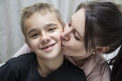 Mama, die Sohn einen Kuss gibt Stockfotos