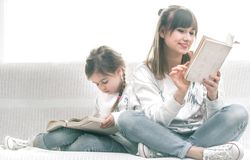 Mama e hija que leen un libro fotos de archivo