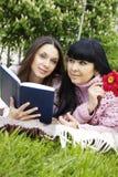 Mama e hija que leen un libro Foto de archivo