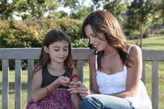 Mama e hija que miran la flor Imagen de archivo libre de regalías
