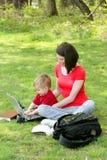 Mama e hijo en la computadora portátil fotografía de archivo