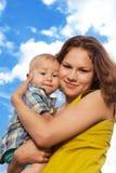 Mama e hijo felices en fondo nublado Fotografía de archivo