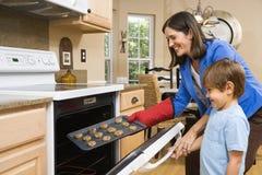 Mama e hijo que hacen las galletas. Imagenes de archivo