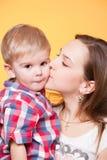 Mama feliz que besa al pequeño hijo Fotografía de archivo