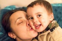 Mama gently kissing small son. Mama gently kissing small son Stock Image