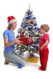 Mama gibt der Tochter für Weihnachten 3 ein Geschenk stockbilder