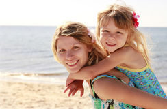 Mama and her little daughter on the beach stock images