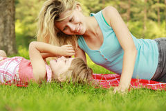Mama and her little daughter lie on the grass Royalty Free Stock Images
