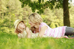 Mama and her little daughter lie on the grass. A Mama and her little daughter lie on the grass stock image