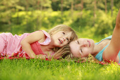 Mama and her little daughter lie on the grass. A Mama and her little daughter lie on the grass royalty free stock photography