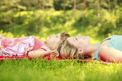 Mama and her little daughter lie on the grass. A Mama and her little daughter lie on the grass royalty free stock photo
