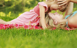 Mama and her little daughter lie on the grass Royalty Free Stock Photo