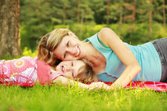 Mama and her little daughter lie on the grass. A Mama and her little daughter lie on the grass royalty free stock image