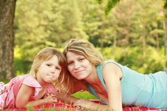 Mama and her little daughter lie on the grass Stock Images