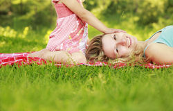 Mama and her little daughter lie on the grass Stock Photos