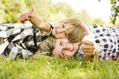Mama and her little daughter lie on the grass Stock Photo