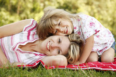 Mama and her little daughter lie on the grass Stock Photography