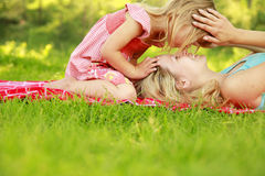 Mama and her little daughter playing on grass Royalty Free Stock Photos