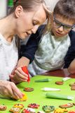 Mama and her son decorate cakes with a colored icing in tubes. Decorated cakes lie on a green table. stock photography