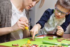 Mama and her son decorate cakes with a colored icing in tubes. Decorated cakes lie on a green table. The son shows his mum with hi royalty free stock photo