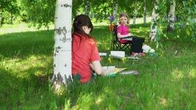 Mama i córka angażujemy w twórczości w parku w cieniu pod drzewami zdjęcie wideo