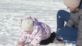 Mama i córka bawić się snowballs, mama z trzyletnią córką bawić się snowballs na zima dniu, córka zbiory